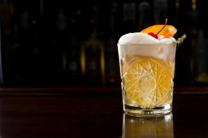 Cocktail, garniert mit einer Cocktailkirsche und einer Orangenscheibe