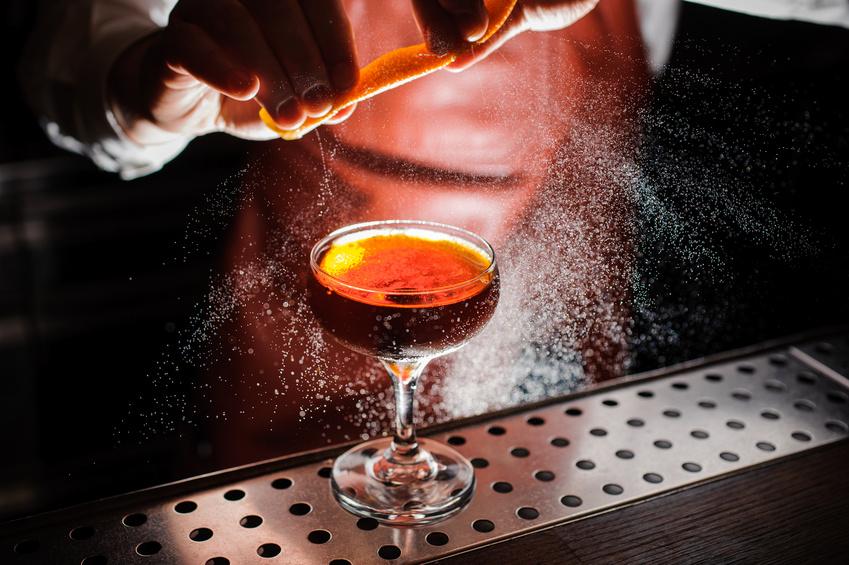 Orange garnish spray over a drink. no face