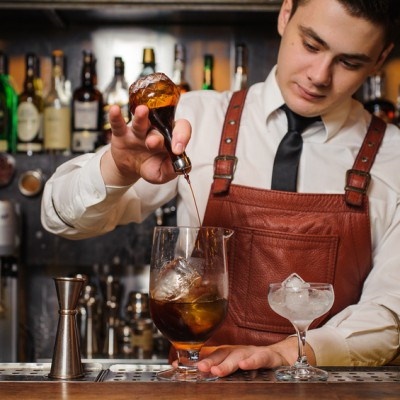 Barman is making cocktail at the bar