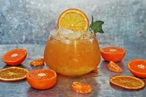 Cocktail garniert mit Orangenscheiben und Mandarinen