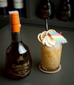 Cocktail dekoriert mit einem Schirmchen, daneben steht eine Carlos Flasche