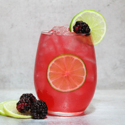 Cocktail garniert mit Brombeeren und Gurkenscheiben