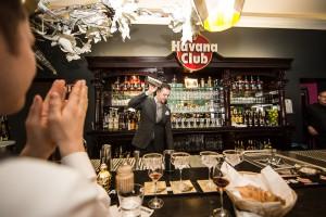 Bar mit dem Havana Club Schild, der Bartender wirft einen Cocktail