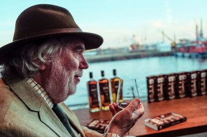 Mann mit Hut, der in der Hand ein Glas mit Whiskey hält