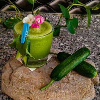 Poker Face: grüner Cocktail in einem mittleren Glas, garniert mit einer Gurke