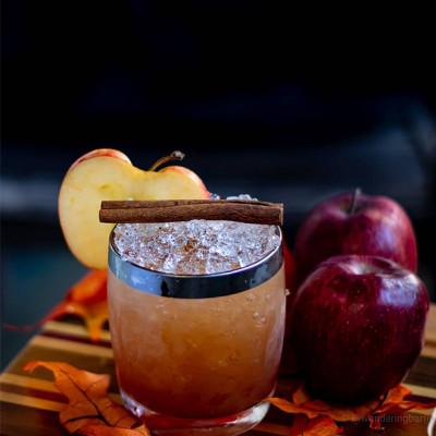 Cocktail garniert mit einer Zimtstange und einer Apfelscheibe