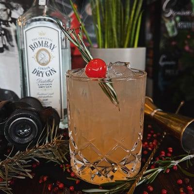 Cocktail garniert mit einer Cocktailkirsche und Rosmarin